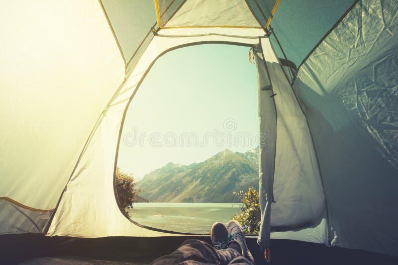 Piedi di uomo che si rilassa godendo delle montagne e della vista del lago a partire da estate all'aperto di campeggio di avventu fotografia stock libera da diritti