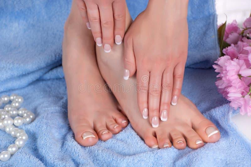 Piedi e mani femminili con il manicure francese ed il pedicure nel salone della stazione termale sull'asciugamano blu blu con il  immagini stock