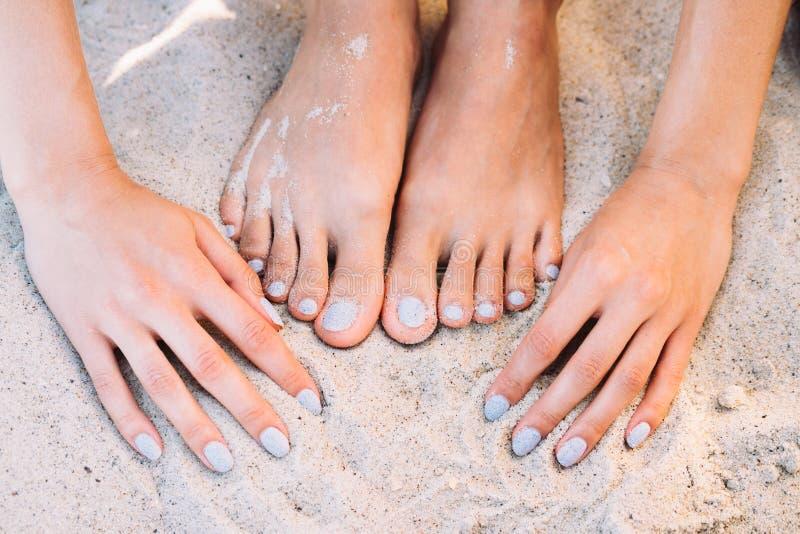 Piedi e mani femminili con il manicure in sabbia della spiaggia di estate fotografia stock libera da diritti