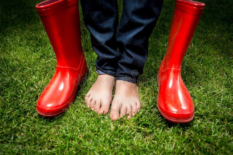 Piedi femminili che stanno sull'erba verde accanto agli stivali di pioggia rossi fotografia stock