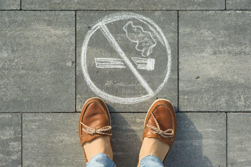 Piedi femminili con non fumatori dell'immagine dipinto sul marciapiede grigio fotografie stock