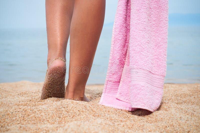 Piedi femminili sulla sabbia Lago Baikal immagini stock