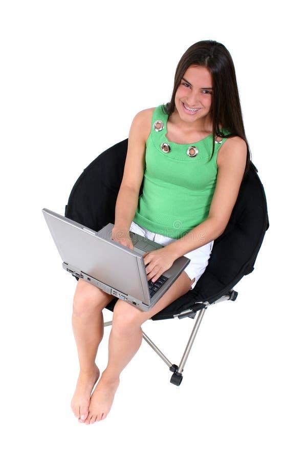 A piedi nudi teenager con il computer portatile sopra bianco fotografia stock libera da diritti