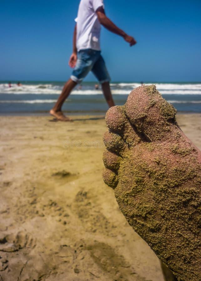 Piedi in pieno della sabbia sulla spiaggia immagini stock