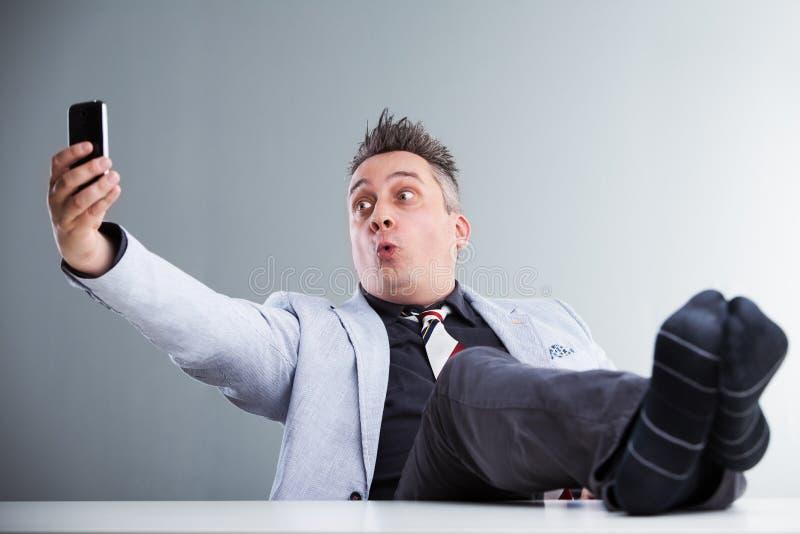 Piedi sulla tavola e sulla presa del selfie immagini stock