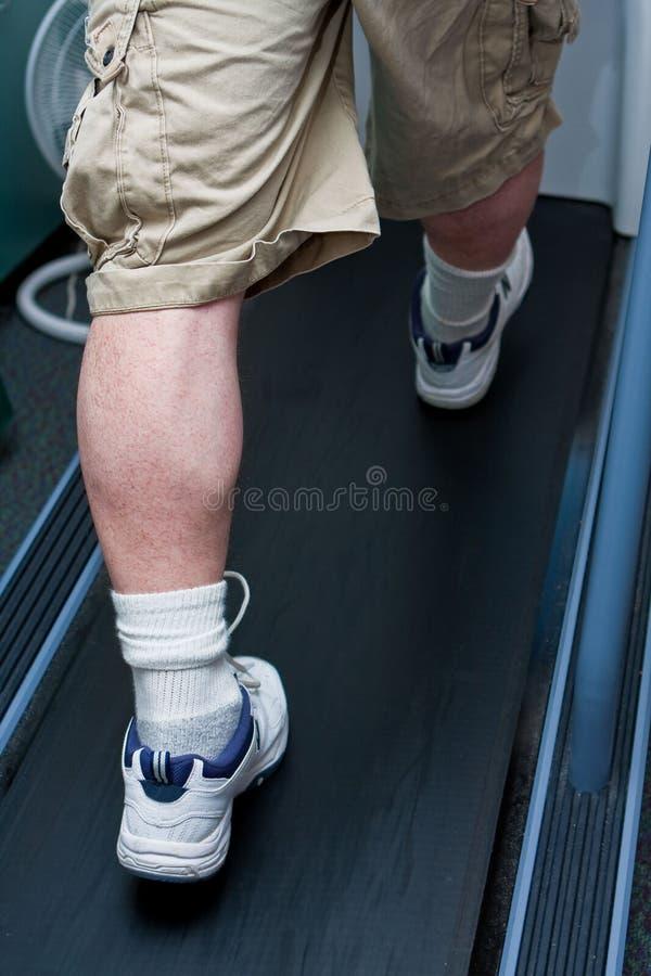 Piedini dell'uomo che camminano sulla pedana mobile fotografia stock libera da diritti