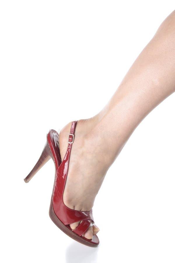 piedini della donna e pattini rossi del tallone sopra bianco fotografia stock
