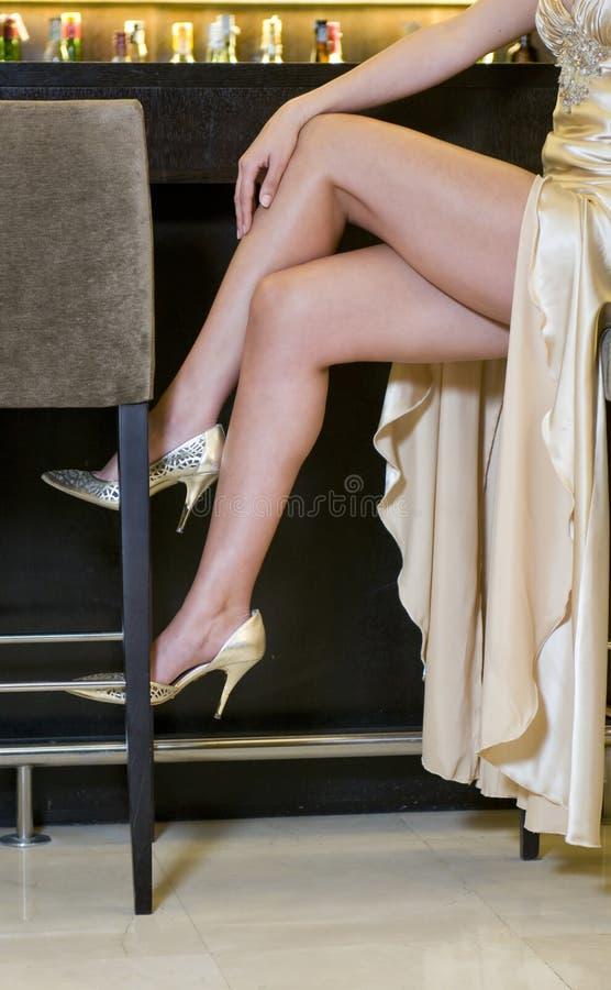 Piedini della donna elegante che si siedono in una barra di lusso immagini stock libere da diritti