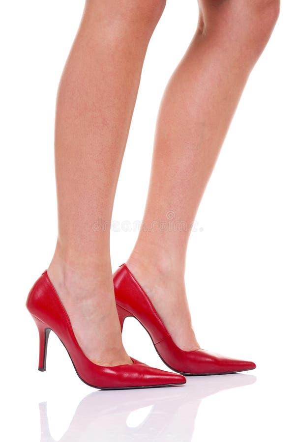 Piedini delle donne in pattini rossi dell'alto tallone fotografie stock