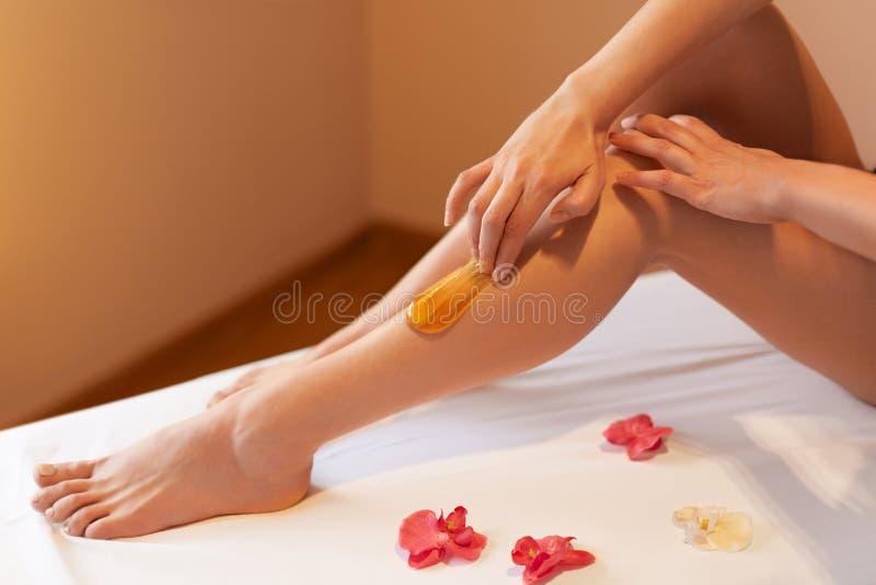 Piedini lunghi della donna Cure della donna circa le sue gambe Zucchero del trattamento fotografia stock
