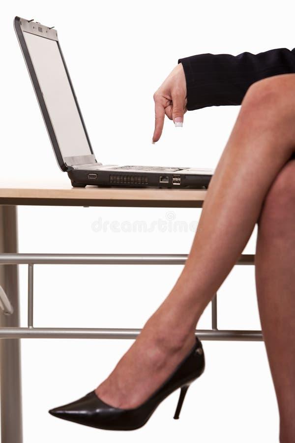 Piedini sexy della donna di affari che portano i talloni immagine stock