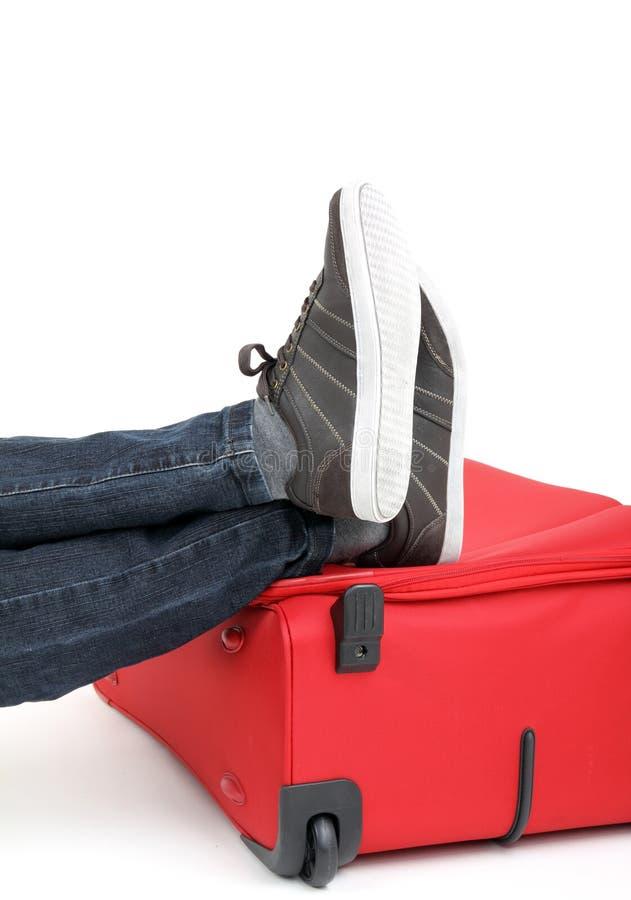 Piedini sulla valigia rossa fotografia stock