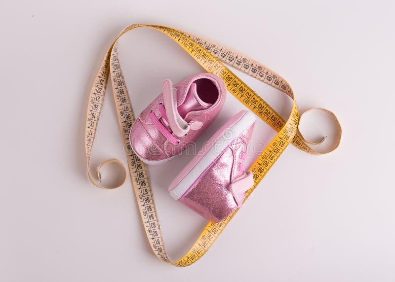 Piedino Nastro giallo dimensionale e scarpe per bambini fotografie stock