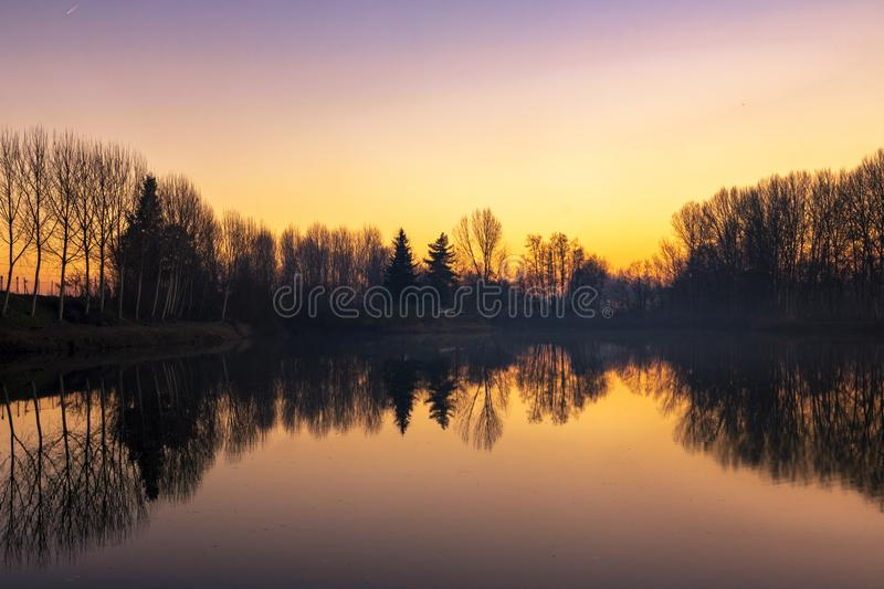 Piedmont, Italy, lakefront at sunset, in the park of the river po. Beautiful lakefront at sunset, in the park of the river po po morto with reflected trees near royalty free stock images