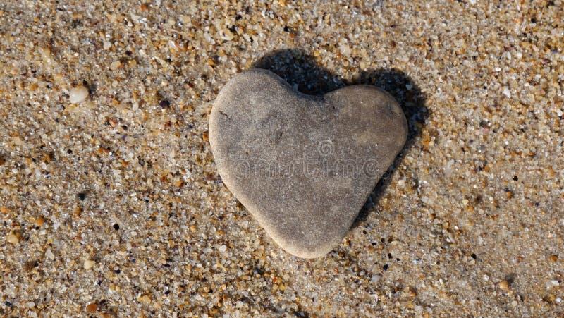 Piedra bajo la forma de corazón en la arena, como símbolo del amor fotos de archivo