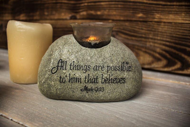 Piedra con escritura cristiana con la vela ligera imagen de archivo libre de regalías