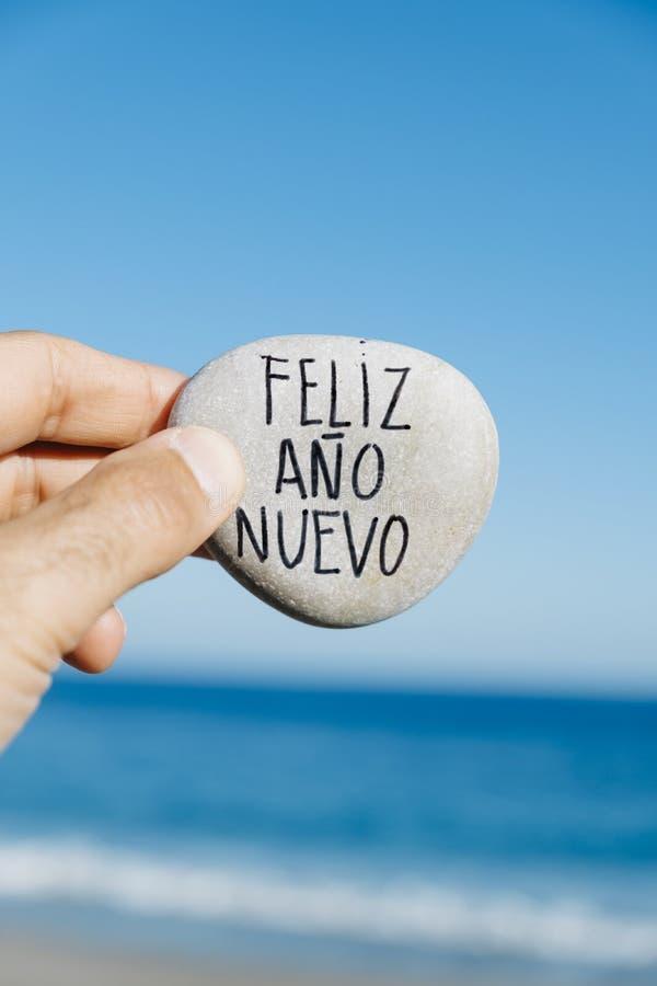 Piedra con la Feliz Año Nuevo del texto en español imagen de archivo libre de regalías