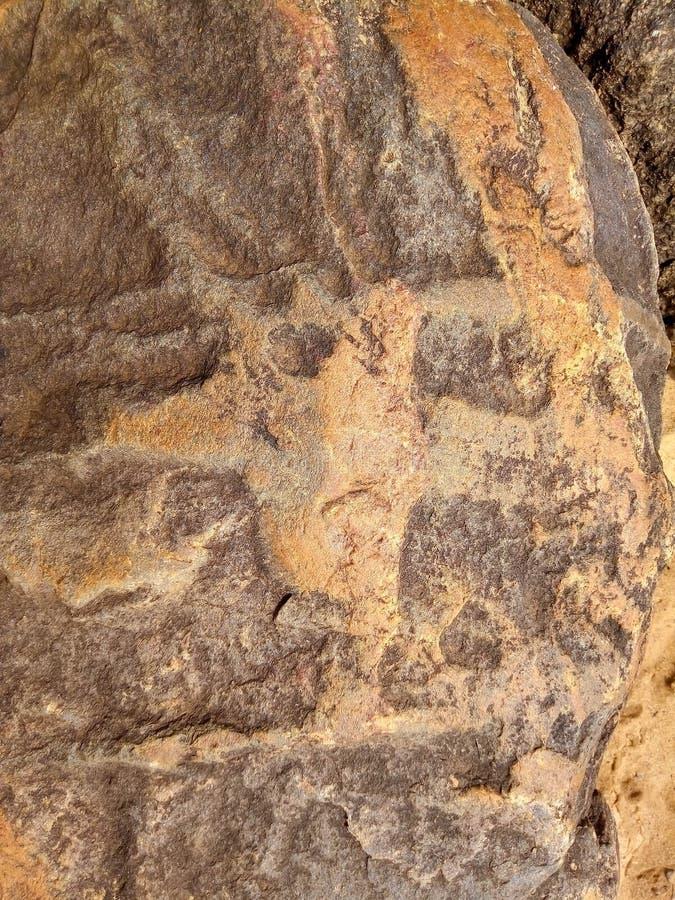 Piedra con una imagen en la playa imagenes de archivo