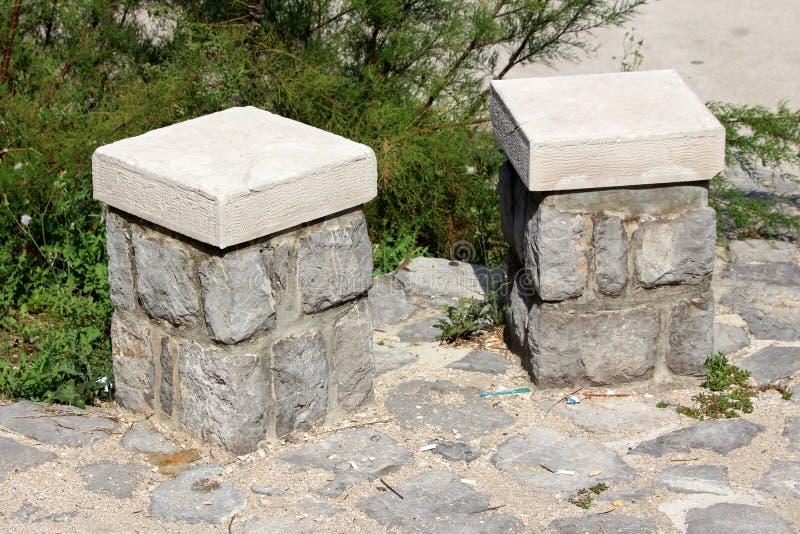 Piedra de dos solos asientos y bancos públicos concretos en la fundación de piedra de las tejas con las plantas densas en fondo imagenes de archivo