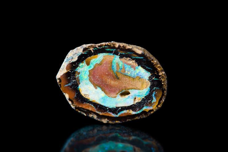 Piedra de gema del ópalo de fuego, piedra curativa, fondo negro, mineral imagen de archivo