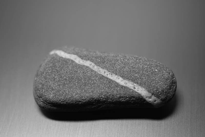 Piedra de guijarros con línea blanca diagonal natural en la mesa, foto en bw imagenes de archivo