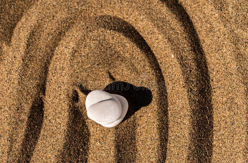 Piedra de la meditación del zen en arena, el concepto para la armonía de la pureza y el spi foto de archivo