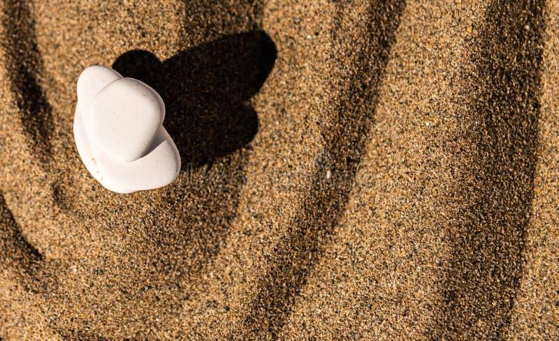 Piedra de la meditación del zen en arena, el concepto para la armonía de la pureza y el spi fotografía de archivo