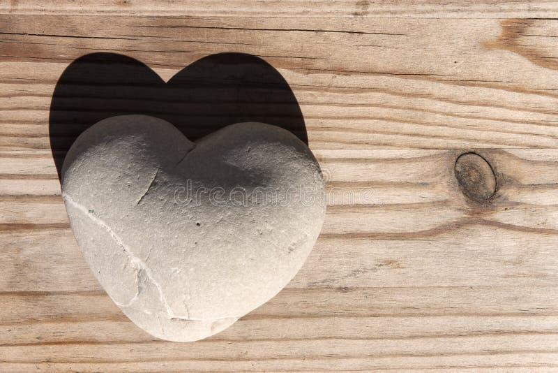 Piedra del corazón con la sombra en la tabla de madera fotografía de archivo
