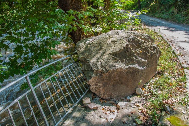 Piedra enorme que cayó de la montaña y dañó la cerca fotos de archivo