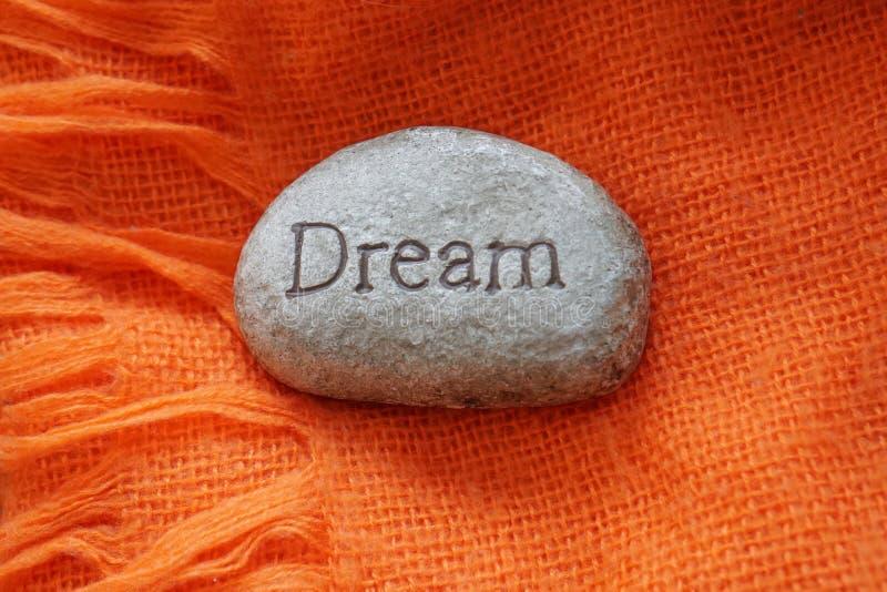 Piedra gris con el sueño de la inscripción en una manta anaranjada Oto?o Concepto de sueño y de esperanza imágenes de archivo libres de regalías