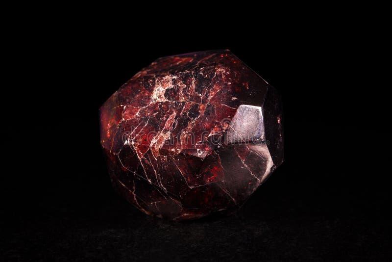Piedra mineral del granate delante del negro fotografía de archivo libre de regalías