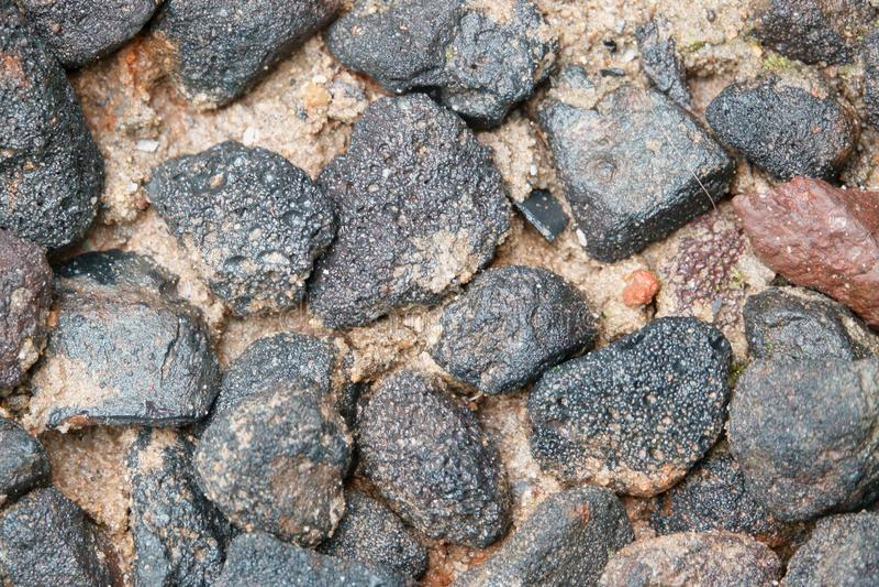 Piedra negra en la arena mojada foto de archivo