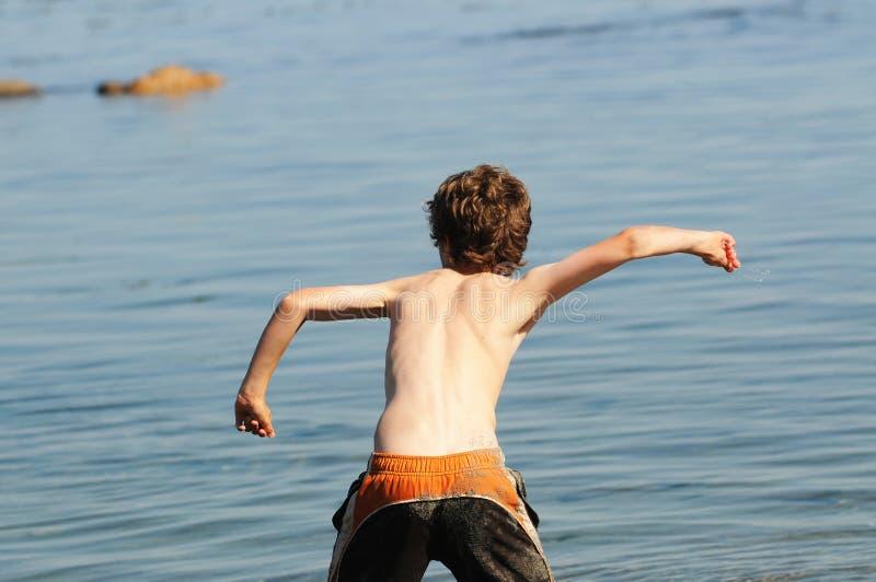 Piedra que lanza del muchacho en el mar imagen de archivo