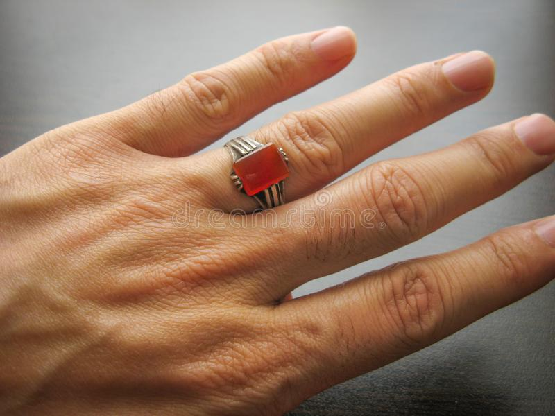 Piedra roja yemen? de la ?gata del aqeeq Mano masculina con el anillo en el dedo anular con el fondo oscuro Anillo de Yemen fotografía de archivo