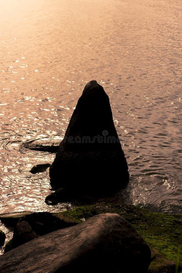 Piedra triangular en el mar imágenes de archivo libres de regalías