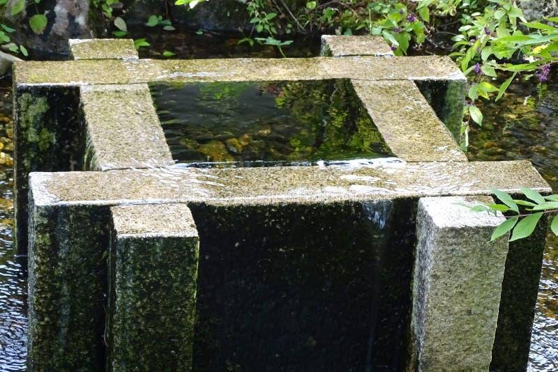Piedra vieja bien llena de agua en un parque fotografía de archivo