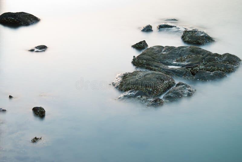 Piedra y corriente en paisaje marino fotografía de archivo