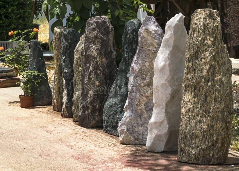 Piedras altas grandes de diversos colores que se colocan en fila en la yarda Cerca o pared de piedra foto de archivo libre de regalías