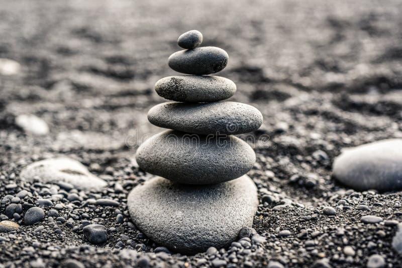 Piedras apiladas encima de una playa negra en Islandia fotos de archivo