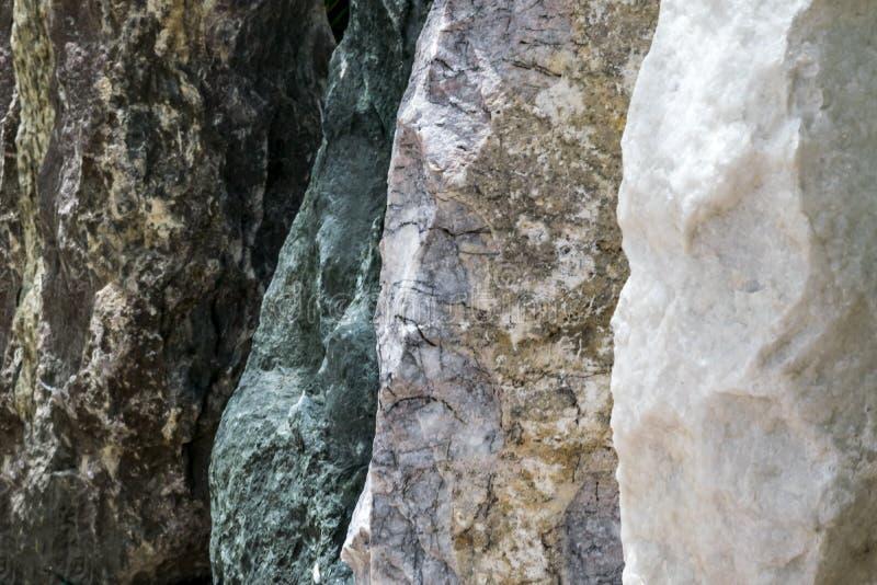 Piedras de diversos colores en fila Cerca o pared de piedra imágenes de archivo libres de regalías