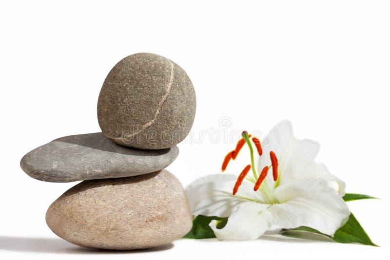 Piedras de equilibrio y lirio blanco imagenes de archivo