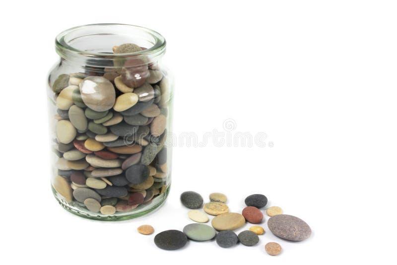 Piedras de los guijarros o de la playa en un tarro de cristal imagen de archivo