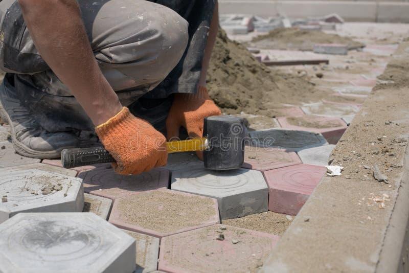 Piedras de pavimentación del trabajador fotografía de archivo libre de regalías