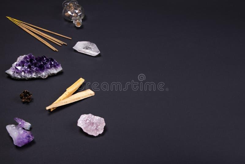 Piedras del cristal de la amatista y de cuarzo, madera del santo del palo, palillos aromáticos, cono y botella decorativa en fond imagenes de archivo
