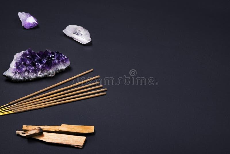 Piedras del cristal de la amatista y de cuarzo, madera del santo del palo, palillos arom?ticos en fondo negro imagen de archivo libre de regalías