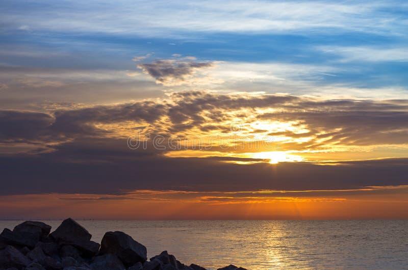 Piedras del granito en la costa, un cielo hermoso con las nubes de la salida del sol, un horizonte de mar, tranquilidad imágenes de archivo libres de regalías