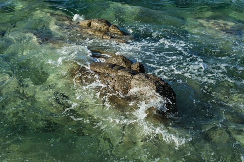 Piedras del lavado de las ondas del mar Agua del mar o del océano con espuma y ondulaciones Roca en agua transparente El viajar y fotografía de archivo libre de regalías