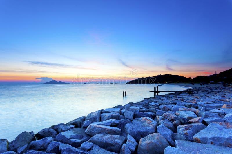 Piedras del mar de la puesta del sol a lo largo de la costa foto de archivo libre de regalías