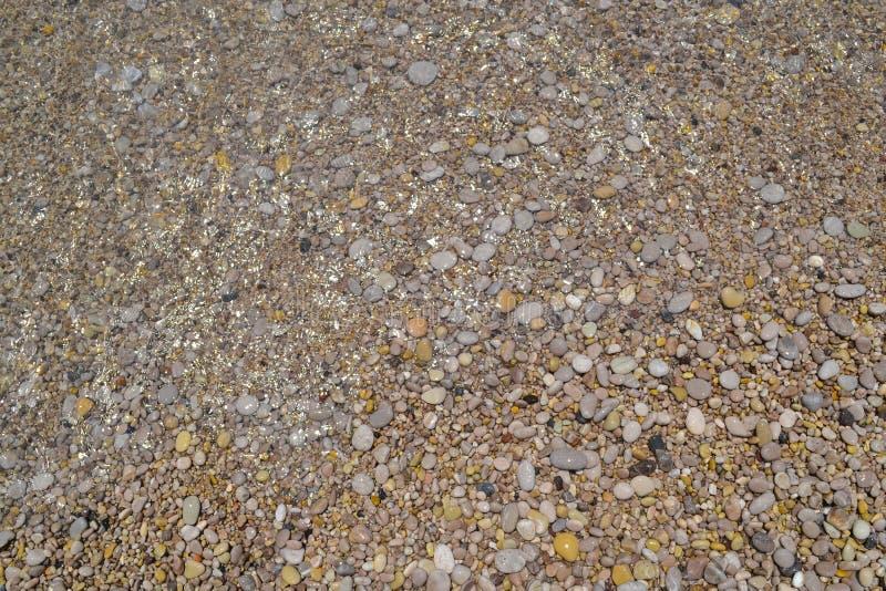 Piedras del mar en la agua de mar Guijarros bajo el agua La visi?n desde la tapa Sello con un tema n?utico Limpie la agua de mar  imagen de archivo