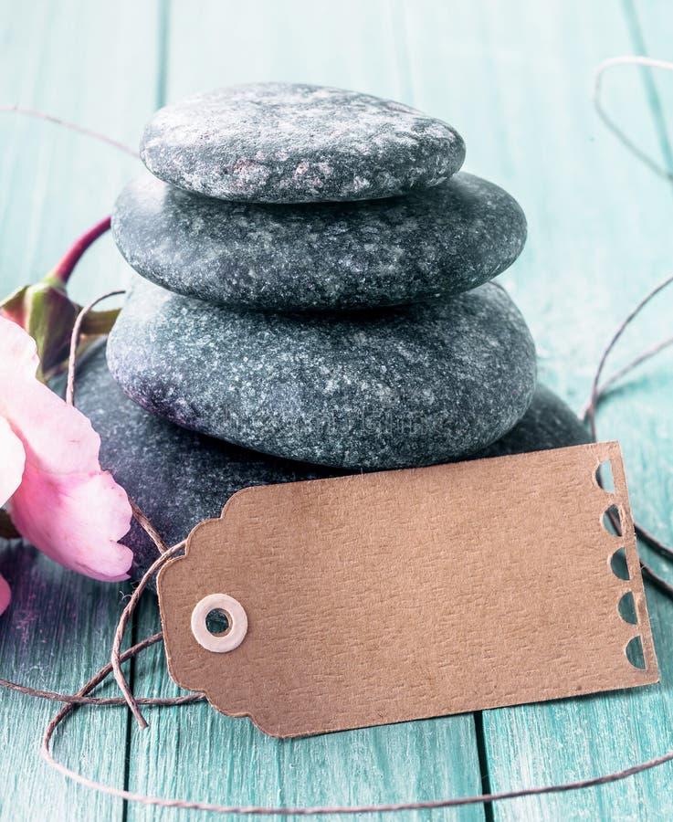 Piedras del masaje del balneario con una etiqueta en blanco imagen de archivo libre de regalías